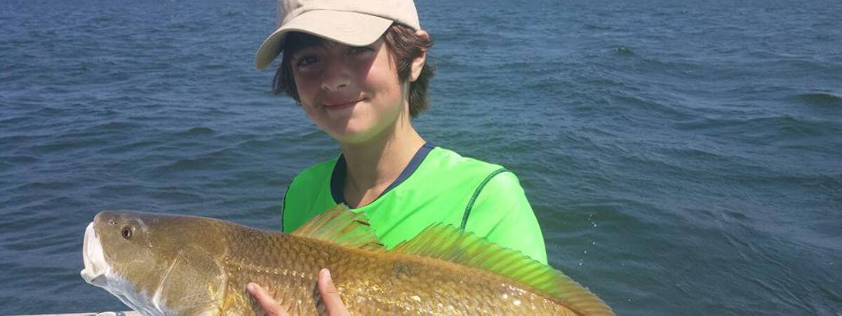 Young angler holding a big red drum caught on the Pamlico Sound
